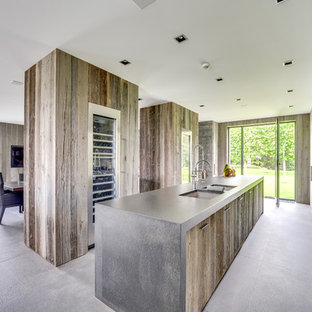 Large contemporary single-wall open plan kitchen in Paris with an undermount sink, flat-panel cabinets, distressed cabinets, stainless steel appliances, with island and ceramic floors.