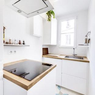 Cette image montre une cuisine ouverte parallèle nordique de taille moyenne avec un évier 1 bac, un placard à porte affleurante, des portes de placard blanches, un plan de travail en bois, une crédence blanche, une crédence en fenêtre, un électroménager en acier inoxydable, un sol en carrelage de céramique et aucun îlot.