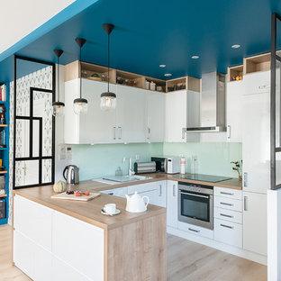 Idées déco pour une cuisine contemporaine avec un évier posé, un placard à porte plane, des portes de placard blanches, un plan de travail en bois, une crédence verte, une crédence en feuille de verre, un électroménager en acier inoxydable, un sol en bois clair, une péninsule, un sol beige et un plan de travail beige.