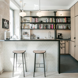 This is an example of a scandinavian l-shaped eat-in kitchen in Paris with an undermount sink, beaded inset cabinets, light wood cabinets, concrete benchtops, green splashback, ceramic splashback, panelled appliances, concrete floors, a peninsula, blue floor and blue benchtop.