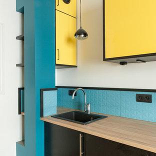 パリのコンテンポラリースタイルのおしゃれなキッチン (黄色いキャビネット、青いキッチンパネル、セメントタイルの床、黄色い床) の写真