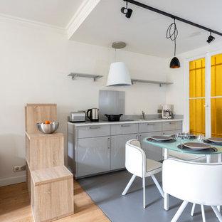 Diseño de cocina lineal, contemporánea, pequeña, abierta, con puertas de armario grises, encimera de cuarcita, salpicadero verde, suelo de linóleo, suelo gris, encimeras blancas, armarios con paneles lisos y salpicadero de vidrio templado