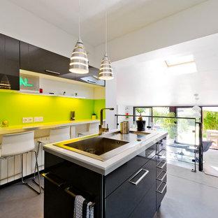 Idées déco pour une cuisine américaine parallèle contemporaine de taille moyenne avec un évier 1 bac, un placard à porte affleurante, des portes de placard grises, un plan de travail en stratifié, une crédence verte, un électroménager en acier inoxydable, béton au sol et un îlot central.