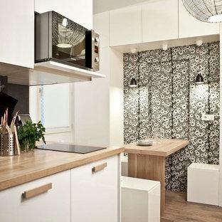 Imagen de cocina comedor lineal, contemporánea, de tamaño medio, sin isla, con puertas de armario blancas, salpicadero negro y suelo de madera en tonos medios