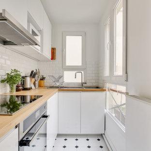 パリの小さい北欧スタイルのおしゃれなキッチン (ドロップインシンク、フラットパネル扉のキャビネット、白いキャビネット、木材カウンター、白いキッチンパネル、サブウェイタイルのキッチンパネル、シルバーの調理設備、アイランドなし、白い床、ベージュのキッチンカウンター) の写真