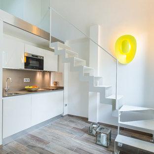 Пример оригинального дизайна: маленькая линейная кухня-гостиная в современном стиле с плоскими фасадами, белыми фасадами, серым фартуком и темным паркетным полом без острова