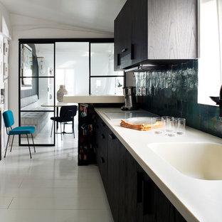 Inspiration pour une cuisine linéaire design fermée et de taille moyenne avec un évier intégré, des portes de placard en bois sombre, un sol en carrelage de céramique et une péninsule.