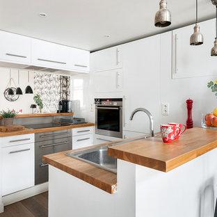 Réalisation d'une cuisine design en U de taille moyenne avec un évier posé et un plan de travail en bois.