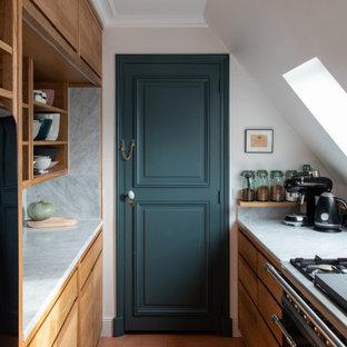 Réalisation d'une petit cuisine parallèle design fermée avec un placard à porte plane, des portes de placard en bois brun, une crédence grise, un électroménager noir, un sol en carreau de terre cuite, aucun îlot, un sol orange et un plan de travail gris.