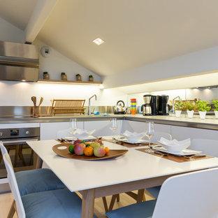 Inspiration pour une cuisine américaine marine en L avec un placard à porte plane, des portes de placard blanches, une crédence en carreau de miroir, un électroménager en acier inoxydable, un sol en bois clair, aucun îlot et un sol beige.