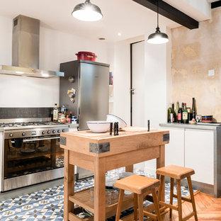 Imagen de cocina comedor de galera, urbana, de tamaño medio, con encimera de zinc, salpicadero negro, electrodomésticos de acero inoxidable, suelo de baldosas de cerámica, puertas de armario blancas y una isla