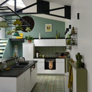 Ejemplo de cocina en L, ecléctica, abierta, con fregadero encastrado, armarios con paneles lisos, puertas de armario blancas, salpicadero gris, electrodomésticos blancos, una isla y suelo verde
