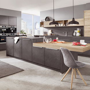 Large modern l-shaped eat-in kitchen in Other with an integrated sink, beaded inset cabinets, grey cabinets, laminate benchtops, grey splashback, slate splashback, panelled appliances, concrete floors, with island, grey floor and grey benchtop.