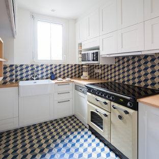 パリのトランジショナルスタイルのおしゃれなキッチン (白いキャビネット、木材カウンター、青いキッチンパネル、セラミックタイルのキッチンパネル、カラー調理設備、セラミックタイルの床、青い床、エプロンフロントシンク、シェーカースタイル扉のキャビネット、アイランドなし、ベージュのキッチンカウンター) の写真