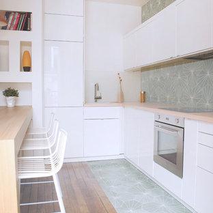 Inspiration pour une cuisine design en L de taille moyenne avec des portes de placard blanches, un plan de travail en bois, une crédence multicolore, une crédence en carreau de ciment, une péninsule, un placard à porte plane et un électroménager en acier inoxydable.