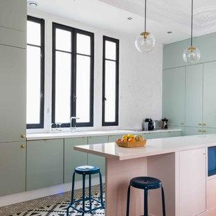 Idée de décoration pour une cuisine design en U avec un placard à porte plane, des portes de placards vertess, une crédence blanche, une péninsule, une crédence en dalle de pierre, un électroménager encastrable et un sol multicolore.