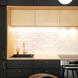 他の地域の小さいモダンスタイルのおしゃれなキッチン (フラットパネル扉のキャビネット、黒いキャビネット、木材カウンター、白いキッチンパネル、サブウェイタイルのキッチンパネル、黒い調理設備、無垢フローリング、茶色い床、ドロップインシンク、アイランドなし、ベージュのキッチンカウンター) の写真