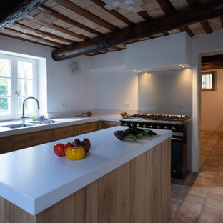 Small transitional l-shaped separate kitchen in Other with an undermount sink, beaded inset cabinets, light wood cabinets, quartz benchtops, metallic splashback, metal splashback, black appliances, terra-cotta floors, with island, pink floor and white benchtop.