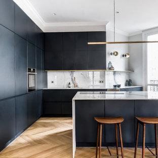 Exemple d'une cuisine tendance en L avec un évier encastré, un placard à porte plane, des portes de placard noires, une crédence blanche, un électroménager noir, un sol en bois brun, un îlot central, un sol marron et un plan de travail blanc.