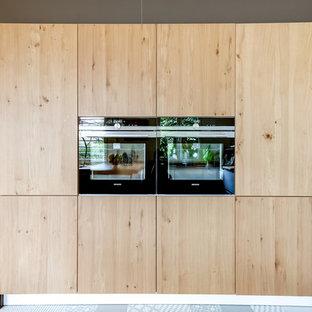 Idées déco pour une cuisine américaine contemporaine en L de taille moyenne avec un placard à porte plane, des portes de placard en bois clair et une crédence blanche.