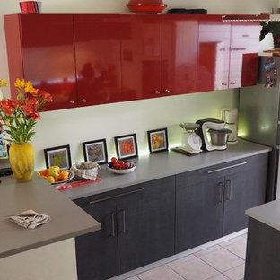 Offene, Zweizeilige, Große Moderne Küche mit Waschbecken, flächenbündigen Schrankfronten, dunklen Holzschränken, Laminat-Arbeitsplatte, Küchenrückwand in Rot, Glasrückwand, Küchengeräten aus Edelstahl, Keramikboden, Kücheninsel und rosa Boden in Nantes