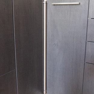 ナントの広いモダンスタイルのおしゃれなキッチン (シングルシンク、フラットパネル扉のキャビネット、濃色木目調キャビネット、ラミネートカウンター、赤いキッチンパネル、ガラス板のキッチンパネル、シルバーの調理設備、セラミックタイルの床、ピンクの床) の写真