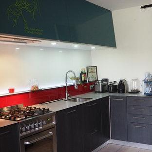 ナントの大きいモダンスタイルのおしゃれなキッチン (シングルシンク、フラットパネル扉のキャビネット、濃色木目調キャビネット、ラミネートカウンター、赤いキッチンパネル、ガラス板のキッチンパネル、シルバーの調理設備、セラミックタイルの床、ピンクの床) の写真