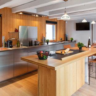 Cette photo montre une cuisine parallèle industrielle avec un placard à porte plane, une façade en inox, une crédence marron, une crédence en bois, un sol en bois clair, un îlot central, un sol beige, un plan de travail gris et un plafond en poutres apparentes.