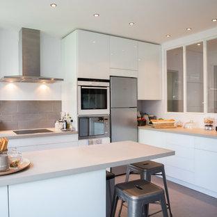 Cette photo montre une cuisine ouverte tendance en U de taille moyenne avec un placard à porte plane, des portes de placard blanches, une crédence grise et une péninsule.