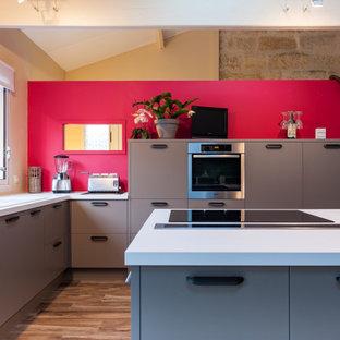 Idées déco pour une grande cuisine contemporaine en L avec un placard à porte plane, un plan de travail en surface solide, un îlot central, un sol marron, un plan de travail blanc, un évier posé, des portes de placard marrons, une crédence rouge et un électroménager en acier inoxydable.