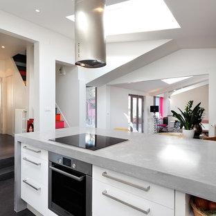 Inspiration pour une cuisine ouverte linéaire design de taille moyenne avec un placard à porte plane, des portes de placard blanches, un électroménager en acier inoxydable, un sol en bois foncé et un îlot central.