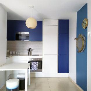 Cette image montre une cuisine marine en U avec un placard à porte plane, des portes de placard bleues, une crédence beige, un électroménager en acier inoxydable, une péninsule, un sol beige et un plan de travail blanc.