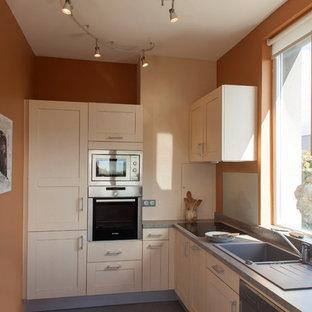 Cette photo montre une petite cuisine chic en L fermée avec un évier posé, un placard à porte shaker, des portes de placard en bois clair et aucun îlot.