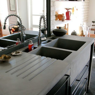 Large industrial u-shaped separate kitchen in Paris with a double-bowl sink, beaded inset cabinets, black cabinets, concrete benchtops, black splashback, slate splashback, black appliances, slate floors, multiple islands, black floor and grey benchtop.