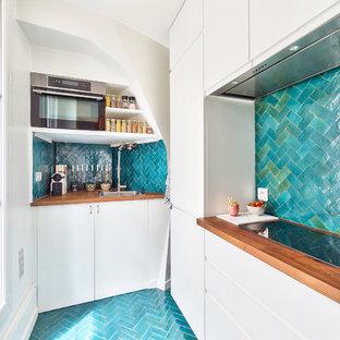 Idées déco pour une cuisine ouverte contemporaine en L de taille moyenne avec des portes de placard blanches, un plan de travail en bois, une crédence bleue, une crédence en carreau de terre cuite, un sol en carrelage de céramique, aucun îlot, un sol bleu, un évier encastré, un placard à porte affleurante, un électroménager en acier inoxydable et un plan de travail marron.