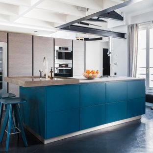 Foto di una cucina abitabile minimal con lavello sottopiano, ante lisce, ante marroni, elettrodomestici in acciaio inossidabile, isola, pavimento nero, top marrone e travi a vista