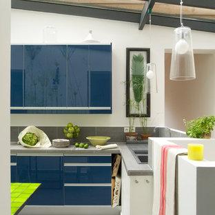 Cette image montre une cuisine américaine design en L de taille moyenne avec un placard à porte plane, des portes de placard bleues, une crédence grise et un îlot central.