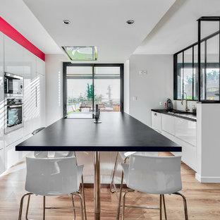 Idées déco pour une cuisine contemporaine avec un placard à porte plane, des portes de placard blanches, un sol en bois clair, un îlot central et un plan de travail noir.
