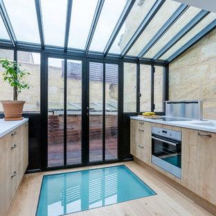 Idée de décoration pour une cuisine parallèle design fermée et de taille moyenne avec un évier intégré, des portes de placard en bois clair, une crédence métallisée, un électroménager encastrable, un sol en bois clair et aucun îlot.