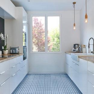 パリの中サイズの北欧スタイルのおしゃれなキッチン (エプロンフロントシンク、フラットパネル扉のキャビネット、白いキャビネット、黒いキッチンパネル、白い調理設備、アイランドなし、青い床、ベージュのキッチンカウンター) の写真
