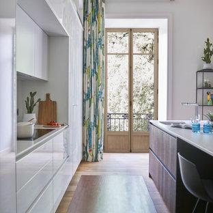 Cette image montre une cuisine ouverte parallèle design de taille moyenne avec un évier encastré, un placard à porte plane, des portes de placard blanches, un électroménager encastrable, un sol en bois brun, un îlot central, un sol beige et un plan de travail blanc.