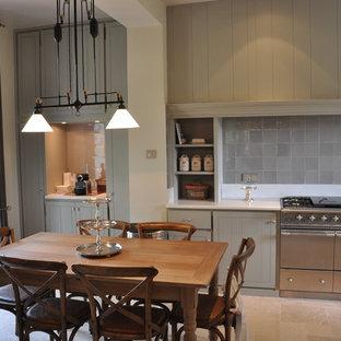Cette image montre une grande cuisine américaine linéaire rustique avec des portes de placard grises, une crédence grise, une crédence en carreau de terre cuite et aucun îlot.