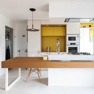 Idée de décoration pour une cuisine américaine parallèle design de taille moyenne avec des portes de placard blanches, un plan de travail en bois, une crédence jaune, un électroménager blanc, béton au sol, une péninsule, un sol blanc, un plan de travail blanc et un placard à porte plane.