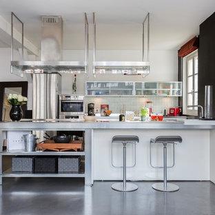 Cette image montre une cuisine urbaine avec un placard à porte vitrée, un plan de travail en inox, une crédence beige, une crédence en mosaïque, un électroménager en acier inoxydable, béton au sol, un îlot central et un sol gris.