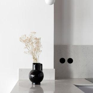 パリの中くらいのコンテンポラリースタイルのおしゃれなキッチン (アンダーカウンターシンク、インセット扉のキャビネット、白いキャビネット、クオーツストーンカウンター、白いキッチンパネル、大理石のキッチンパネル、黒い調理設備、テラコッタタイルの床、赤い床、白いキッチンカウンター) の写真