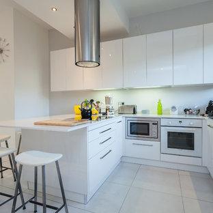 Exemple d'une cuisine ouverte tendance en U avec un placard à porte plane, des portes de placard blanches, un électroménager blanc et une péninsule.