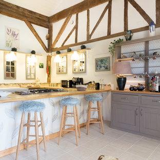 Idées déco pour une cuisine campagne en U avec un évier de ferme, des portes de placard blanches, un plan de travail en bois et une péninsule.