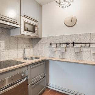 パリの北欧スタイルのおしゃれなコの字型キッチン (アンダーカウンターシンク、グレーのキャビネット、木材カウンター、白いキッチンパネル、セメントタイルのキッチンパネル、黒い調理設備、テラコッタタイルの床、アイランドなし、赤い床、茶色いキッチンカウンター) の写真