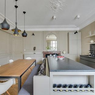 Modelo de cocina comedor de galera, tradicional renovada, con armarios con paneles lisos, puertas de armario grises, salpicadero negro, electrodomésticos negros, suelo de madera clara, una isla y salpicadero de azulejos de terracota