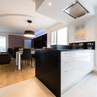 This is an example of a medium sized contemporary l-shaped open plan kitchen in Paris with an integrated sink, beaded cabinets, white cabinets, granite worktops, red splashback, glass tiled splashback, stainless steel appliances, light hardwood flooring and an island.